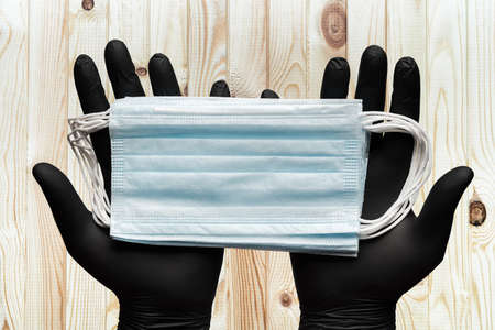 Two doctor hands in black surgical gloves holding medical face masks on brown wood plank background. Close-up view. Concept quarantine, pandemic outbreak and hygiene. Фото со стока
