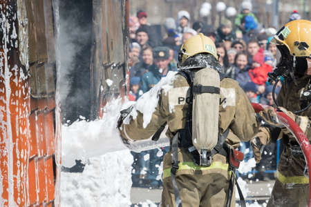 Firefighters extinguishing fire from fire hose, using fire-fighting water-foam barrel with air-mechanical foam during professional holiday Firefighters Day. Kamchatka Peninsula, Russia - Apr 27, 2019. Редакционное