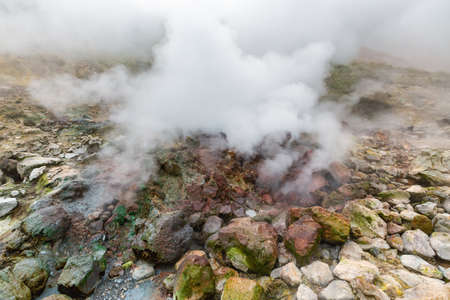 Picturesque view of volcanic landscape, aggressive hot spring, eruption fumarole, gas-steam activity in crater active volcano. Amazing mount landscape, travel destinations for active vacation, hiking. Фото со стока