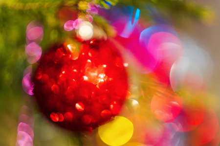 Defocused red Christmas ball hanging on branch of pine tree. Out of focus festive textured effect ornament for celebration Happy New Year. Creative Xmas colorful abstract blurred bokeh, lens flare.