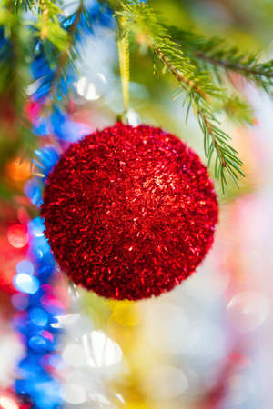 Close-up of holiday ornament for celebration Happy New Year. Shining red Christmas ball hanging on branch of Xmas pine tree. Selective soft focus on foreground, colorful blurry bokeh on background. Stockfoto