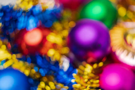 Defocused colorful Christmas balls holiday decorations, abstract blurry bokeh background effect. Out of focus glowing lights celebration texture for use at graphic design.