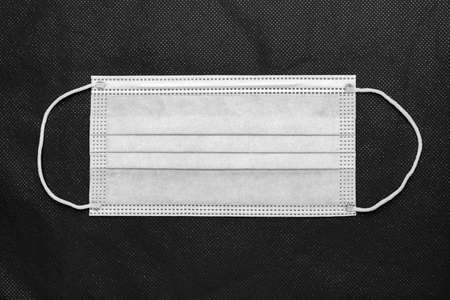 Medical protective face mask on background of non-woven fabric. Flat lay, close-up view of concept quarantine, global lockdown, coronavirus pandemic covid-19 disease. Black and white photography
