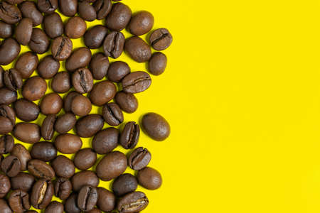 Black coffee beans on yellow background. Left vertical location objects, copy space for text on right. Close-up, flat lay view of colorful coffee still-life.