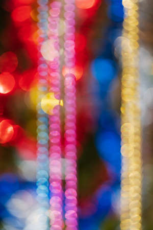 Out of focus colorful abstract blurry bokeh background of balls, tinsel and beads. Shining lens flare photo effect. Christmas ornament decorations, defocused glowing lights, vivid motion blur texture. Stockfoto