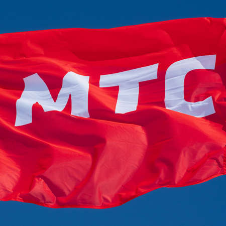 Red flag waving in wind with text in Russian: MTS Mobile TeleSystems, abbreviation mobile operator Russian Federation. Brand flag on background blue sky sunny day. Kamchatka, Russia - March 10, 2019