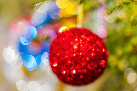 Defocused shining red Christmas ball hanging on branch of Xmas pine tree. Colorful creative abstract blurred bokeh. Out of focus holiday composition ornament decorations for celebration Happy New Year