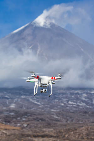 Flying drone quadcopter UAV aerial photography in sky on background of volcano eruption, mountain peak erupting ashes, plume volcanic gas from active crater. Kamchatka Peninsula, Russia - Oct 1, 2016