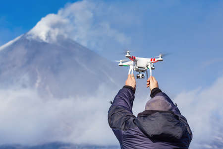 Drone operator catches flying quadcopter UAV on background volcano eruption, mountain peak danger erupting volcanic ashes, gas from active crater. Kamchatka Peninsula, Russian Far East - Oct 1, 2016 Redactioneel
