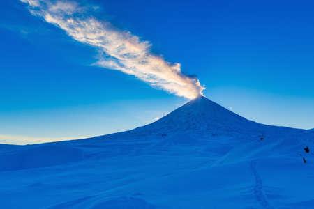 Kamchatka Peninsula, winter eruption active Volcano Klyuchevskaya Sopka at sunset, golden hour. Plume of ash, gas in blue sky, illuminated rays of setting sun. Russia, Klyuchevskaya Group of Volcanoes