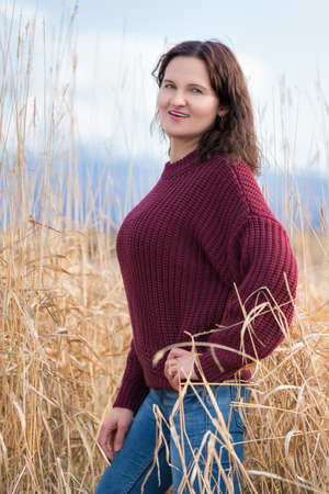 Beautiful stylish young woman dressed in brown pullover, blue jeans standing and posing in dried grass in field in autumn. Pretty woman with long curly brunette hair and red lips.
