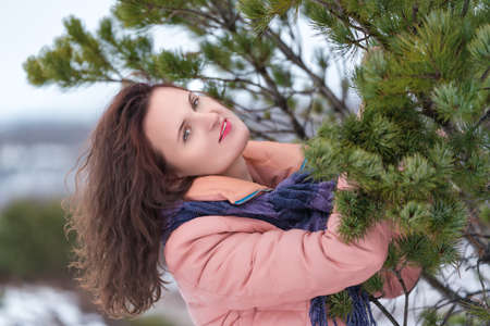 Portrait of cute woman with flowing long curly brunette hair and red lips, dressed in beige jacket with blue scarf. Caucasian young woman poses near evergreen coniferous tree in winter season. Stockfoto