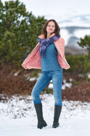 Young woman stands in winter forest near evergreen coniferous tree, looking at camera. Cute brunette woman with long hair, dressed in beige jacket with scarf, blue jeans, high-necked demi-season boots