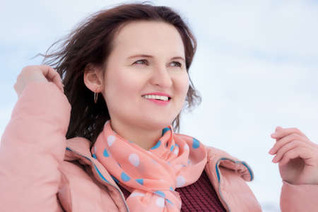 Happy young woman with beautiful smile and curly brunette hair fluttering in wind, dressed in beige jacket, scarf around her neck. Portrait of pretty women outdoors in winter.