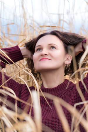 Portrait of stylish young woman dressed in brown pullover posing in dried grass in field. Happy woman with long curly brunette hair and red lips. Stockfoto - 160669574