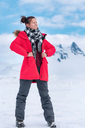 Young woman tourist dressed in red winter windproof jacket, dark gray sports pants and trekking boots standing in mountains in winter season, cold weather. Cute sporty woman posing outdoors.