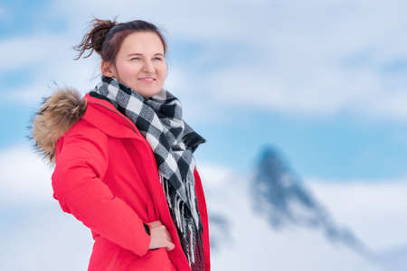 Portrait of woman traveler dressed in red winter windproof jacket, black and white scarf around neck. Mysterious lovely young woman on background of mountains and blue sky with white clouds.
