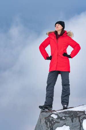 Woman stands on top of rocky mountain against backdrop of sky with dramatic clouds. Concept, copy space for tourism industry. Young woman dressed in red winter jacket, sports pants and trekking boots