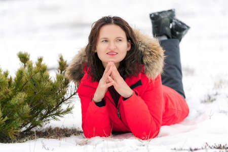 Caucasian woman with long curly hair lies on snow in winter forest, smiles and looks to side. Pretty brunette female dressed in red windproof jacket and trekking boots.