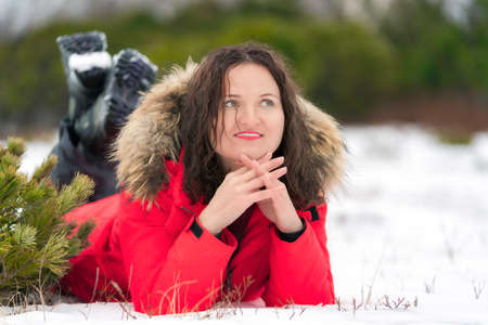 Brunette woman with long curly hair lies on winter snow in fir forest, smiling and looks to side. Young Caucasian woman dressed in red winter jacket and trekking boots.