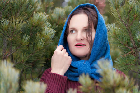 Portrait of sweet brunette woman with brown eyes and long hair stands in fir forest, looking to side. Lovely young woman dressed in brown woolen pullover and blue neckerchief thrown over her head.