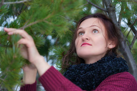 Portrait of brunette woman with long hair and brown eyes standing in pine forest. Cute young woman dressed in brown sweater and black scarf around neck, holding fir branch with needles.