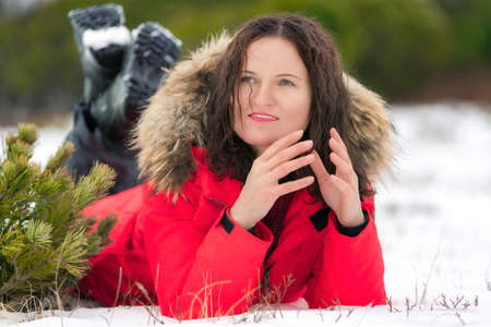 Brunette woman lies on snowdrift in winter pine forest, looks to side and smiles. Young woman with long curly hair dressed in red winter jacket and trekking boots. Stockfoto