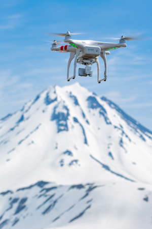 Technological quadcopter drone UAV with digital camera flying on background volcano, rocky mount peak, takes aerial photography world around from birds eye view. Kamchatka, Russia - June 18, 2017 Stockfoto - 161468235