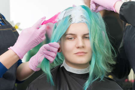 Process of bleaching hair roots in hair salon. Two hairdressers in protective glove use pink brush while applying paint to young adult Caucasian customer with long emerald hair color Stockfoto