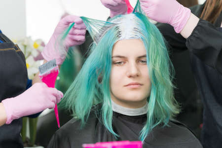 Two hairdressers use pink brush when applying paint to hair during process of bleaching hair roots. Cute young adult Caucasian customer with long emerald hair color in beauty salon.