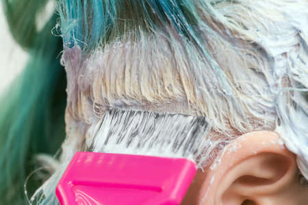 Close-up of hairdresser using pink brush while applying paint to female customer with emerald hair color, during process of bleaching hair roots in hair salon Stockfoto