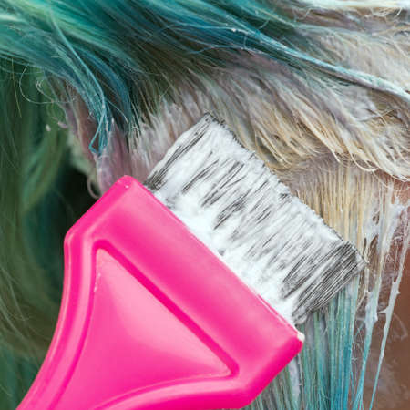 Close-up of hairdresser use pink brush while applying paint to female client with emerald hair color, during process of bleaching hair roots in hair salon.
