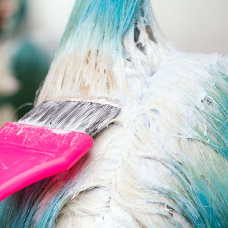 Close-up of stylist using pink brush while applying paint to female customer with emerald hair color, during process of bleaching hair roots in hair salon.
