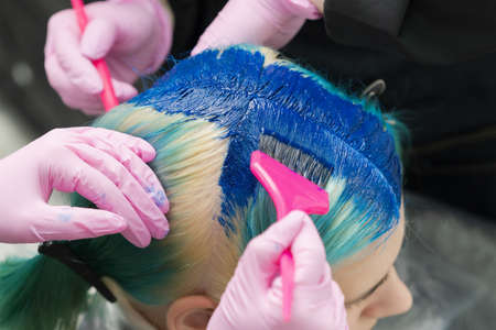 Two hairdressers using pink brush while applying blue paint to female customer with emerald hair color during process of dyeing her hair in unique color