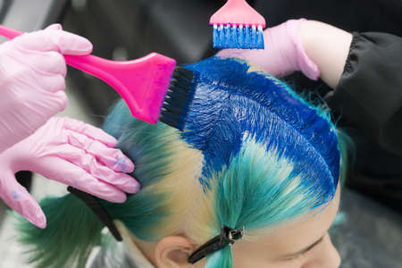 Two hairdressers using pink brush while applying blue paint to female client with emerald hair color, during process of dyeing hair in unique lapis lazuli color