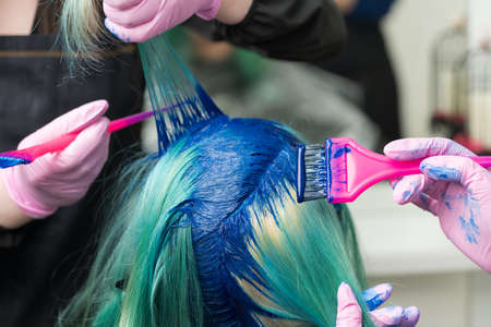 Two professional hairdressers in protective glove using pink brush while applying blue paint to female with emerald hair color, during process of dyeing hair in unique color at beauty salon. Stockfoto