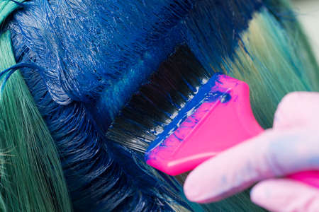 Close-up of hair coloring at beauty salon. Hairdresser using pink brush while applying blue paint to female during process of dyeing hair in unique color