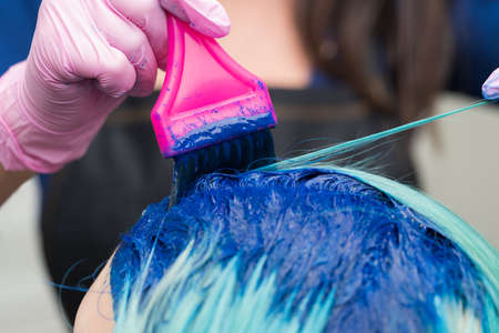 Professional hairdressers in protective glove using pink brush while applying blue paint to female with emerald hair color, during process of dyeing hair in unique color at hair salon. Stockfoto