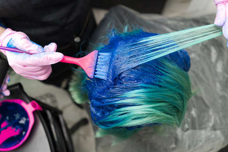 Top view of hair coloring in beauty salon. Hairdresser in protective glove using pink brush while applying blue paint to customer with emerald hair color during process of dyeing hair in unique color