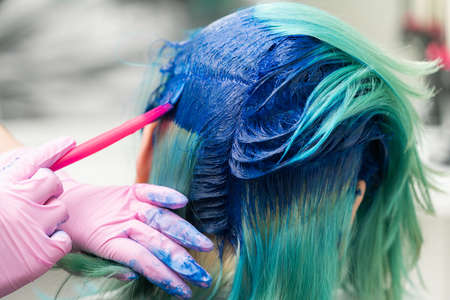 Side view of process of dyeing hair in unique color. Hairdresser in protective glove using pink brush while applying blue paint to female customer with emerald hair color