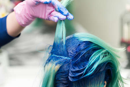 Hairdressers with hand in protective glove lift shock of blue hair of client during coloring process in beauty salon.