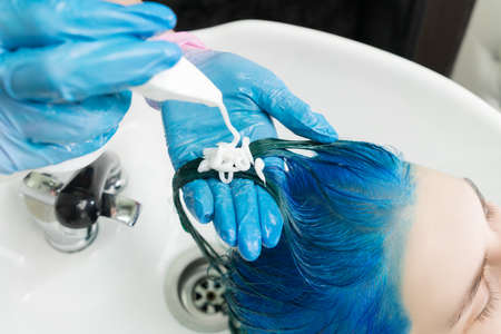 Hairdresser squeezes shampoo from tube onto clients blue hair while washing hair in special sink and shower at beauty salon after hair dyeing process. Stockfoto