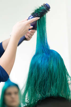 Hairdresser combs and dries hair of emerald color with hairdryer after dyeing hair roots in color of lapis lazuli. Works as professional hairdresser in hair salon.