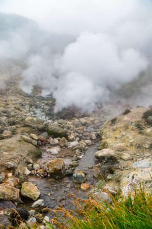 Scenery view of volcanic landscape, aggressive hot spring, gas-steam activity in crater of active volcano, eruption fumarole. Stunning mountain landscape, travel destinations for hike.