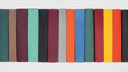 Stack of old hardcover books on white abstract textile background. Close-up view of multicolored vintage hardback books: black, brown, purple, turquoise, gray, orange, blue, green, red, yellow.