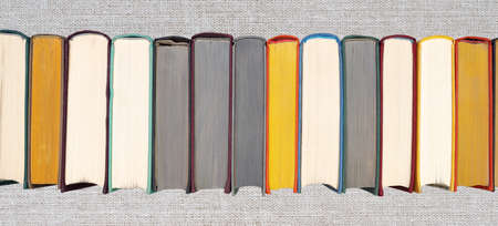 Stack of hardcover books on bookshelf. Close-up view of multicolored vintage hardback books on gray wicker texture background. Flat lay headline panorama banner.