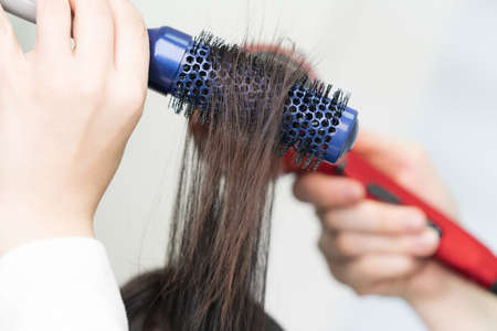 Hands of hairdresser dries brunette hair of client using blue hairbrush and red hairdryer in professional beauty salon. Stockfoto
