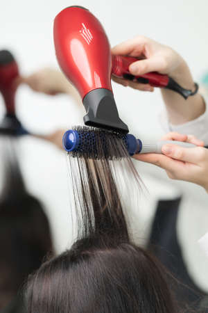 Hands of hairstylist dries long brunette hair of client using red hairdryer and blue comb in professional hair salon. Stockfoto