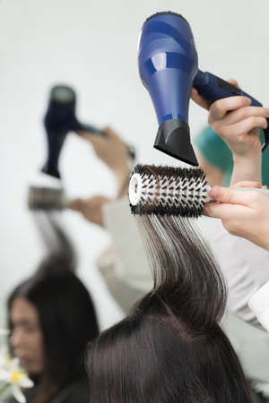 Hands of professional beautician dries long brunette hair of client using blue hair dryer and white hairbrush in beauty salon. Stockfoto