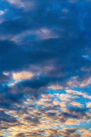 Dramatic clouds in blue sky, illuminated by rays of sun at colorful sunset to change weather. Soft focus, motion blur summer cloudscape background.